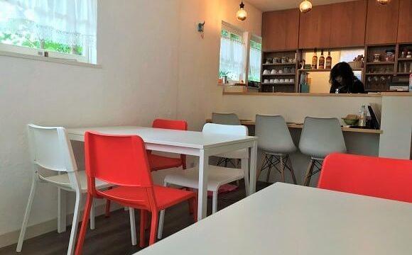 カフェグリーンの真っ白なテーブルと紅白のイスが置かれた明るい店内