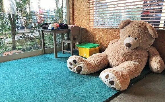 『コイガクボ』の子供用プレイスペースに置かれた大きなクマのぬいぐるみ
